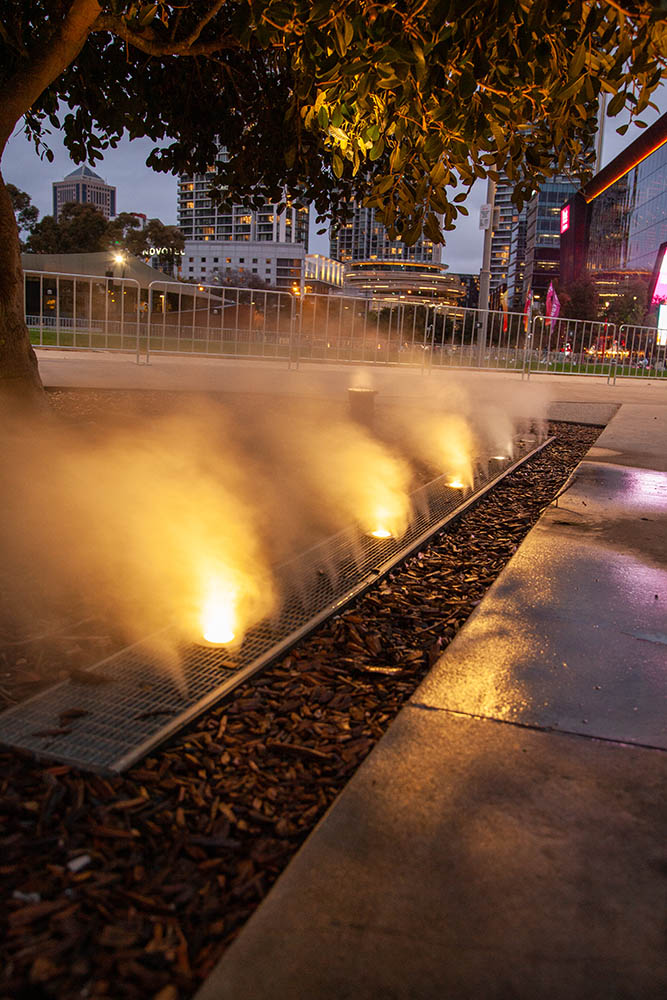 Synchronised uplights custom built within the grate come on with misting fog jets giving Sabdrains 601 channel and grate its own light show at Darling Harbour
